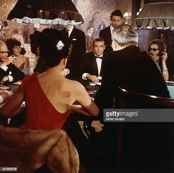 Scottish actor Sean Connery as fictional secret agent James Bond sits at a casino card table in a scene from the film 'Dr. No,' directed by Terence...