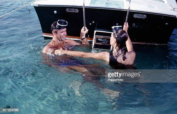 Scottish actor Sean Connery as 'James Bond' pictured with French actress Claudine Auger as 'Domino Derval' in water at the rear of a speed boat in a...