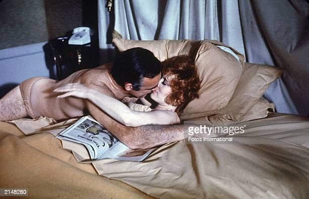 Scottish actor Sean Connery lies in bed kissing American actor Jill St John in a Las Vegas hotel room in a still from the film 'Diamonds Are Forever'...