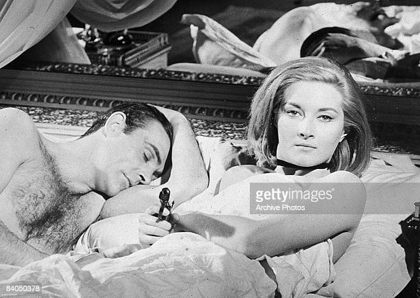 Scottish actor Sean Connery lies in bed with Italian actress Daniela Bianchi in a still from the James Bond film 'From Russia with Love' directed by...