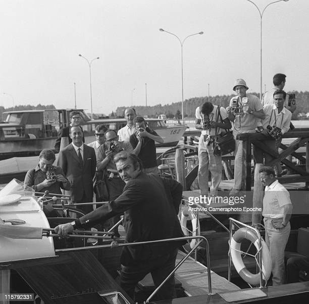 Scottish actor Sean Connery looking behind his back wearing sunglasses and standing on a water taxi surrounded by photographers standing on the wharf...