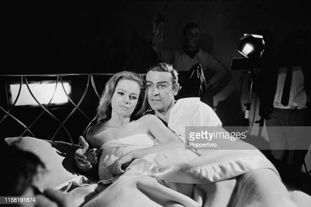 Scottish actor Sean Connery pictured in character as James Bond with Italian actress Luciana Paluzzi during the shooting of a bedroom scene from the...
