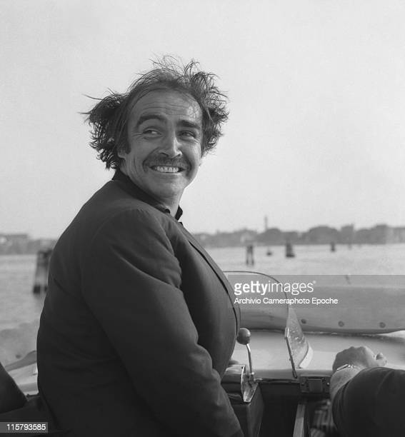 Scottish actor Sean Connery portrayed on a water taxi with his hair in a mess because of the wind looking behind his back in the venetian lagoon with...