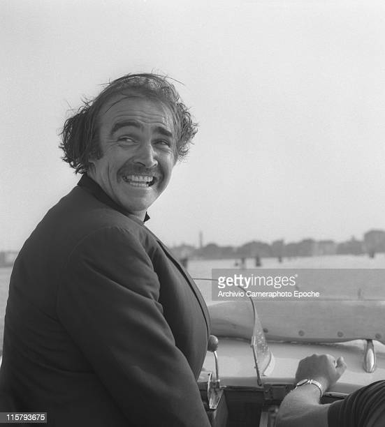 Scottish actor Sean Connery portrayed on a water taxi with his hair in a mess because of the wind looking behind his back and smiling in the venetian...