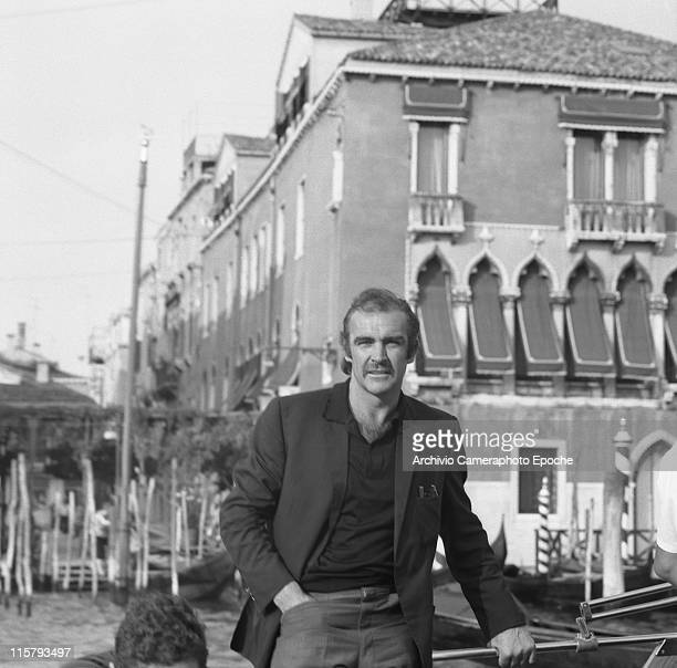 Scottish actor Sean Connery portrayed while standing on a boat on the Canal Grande gondolas behind him Venice 1970s
