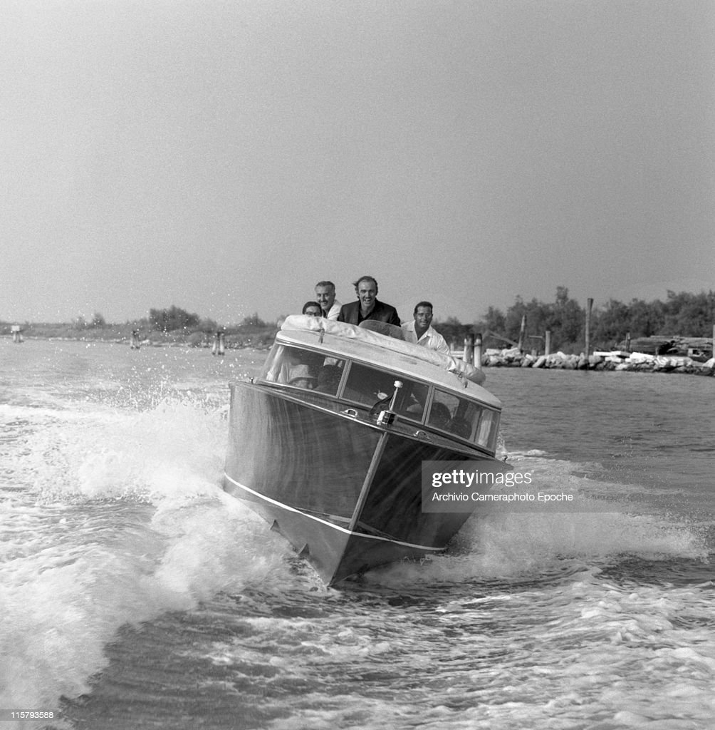 Scottish actor Sean Connery racing on a water taxi with others in the venetian lagoon, Venice 1970s.