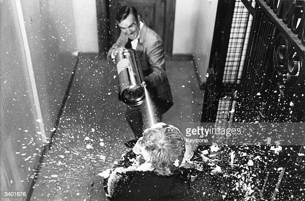 Scottish actor Sean Connery shoots an adversary with a jet of foam from a fire extinguisher in a scene from the James Bond film 'Diamonds Are Forever'