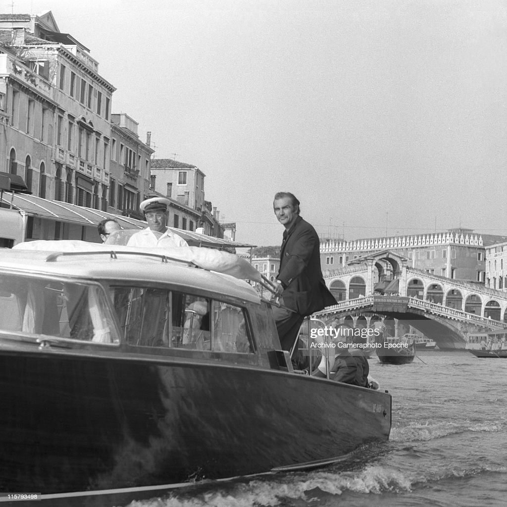 Scottish actor Sean Connery standing on a water taxi with others, Rialto bridge and gondolas on the background, Canal Grande, Venice 1970s.