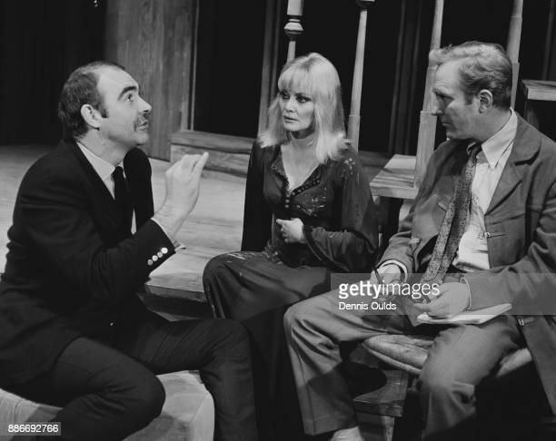Scottish actor Sean Connery talks to his wife actress Diane Cilento and actor Robert Hardy during a break in rehearsals for 'I've Seen You Cut...