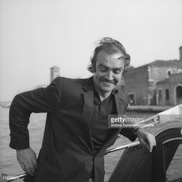 Scottish actor Sean Connery wearing a blazer and a polo shirt portrayed on a water taxi looking down his hair in a mess in the venetian lagoon Venice...