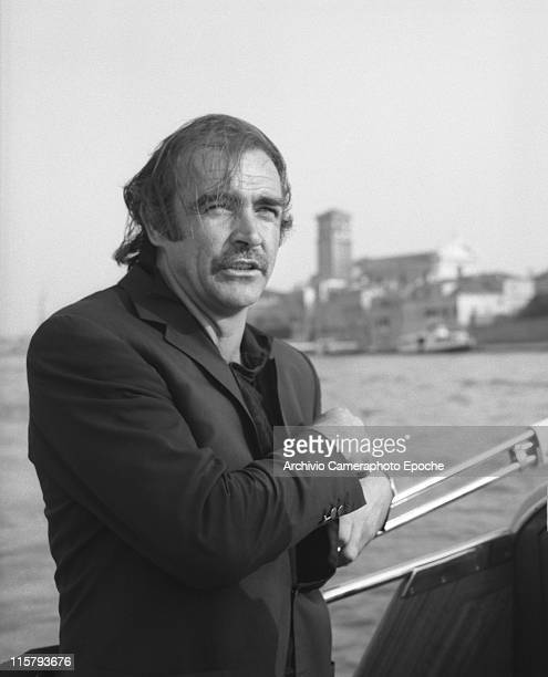 Scottish actor Sean Connery wearing a blazer and a polo shirt portrayed on a water taxi looking for something in his blazer pocket his hair in a mess...