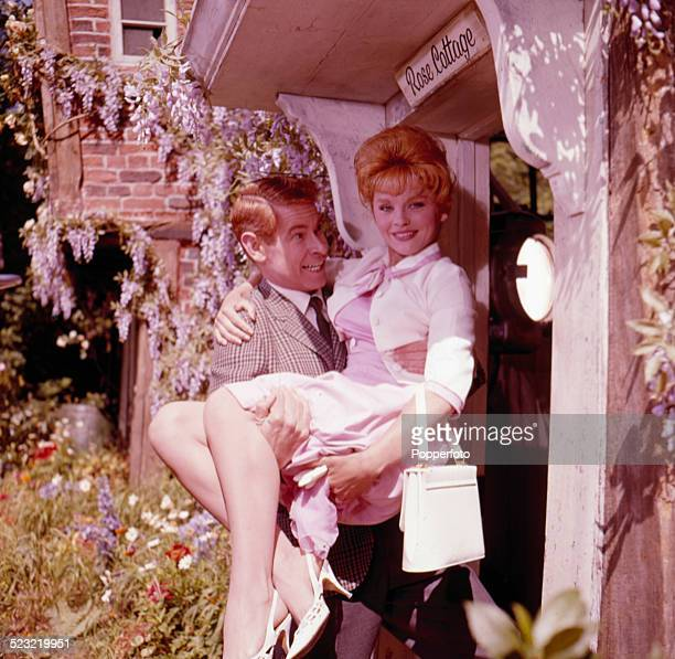 Scottish actor Stanley Baxter carries actress Sally Smith across the threshold of a cottage in a scene from the film Father Came Too In 1963