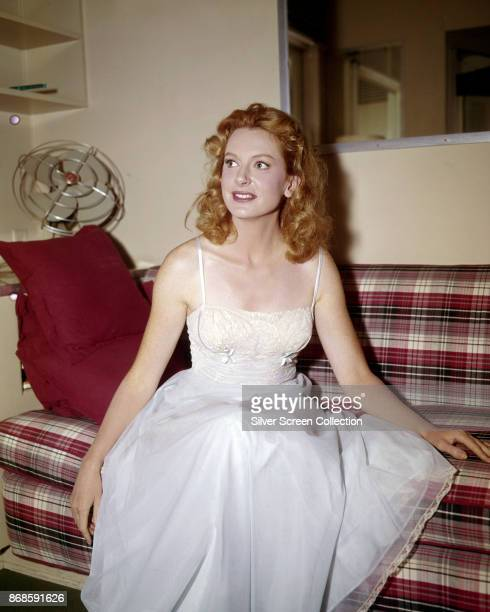 Scottish actress Deborah Kerr in an embroidered gown sits on a plaid sofa early 1950s