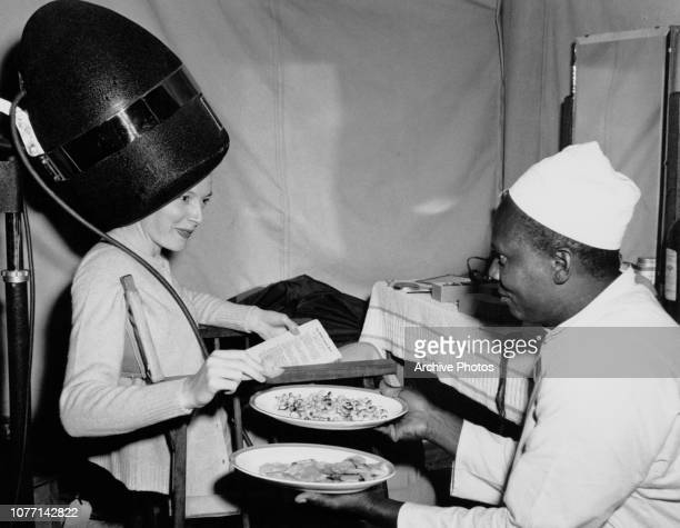 Scottish actress Deborah Kerr is served a snack of fried cashew nuts and potatoes on the set of the MGM film 'King Solomon's Mines' 1950 She is...