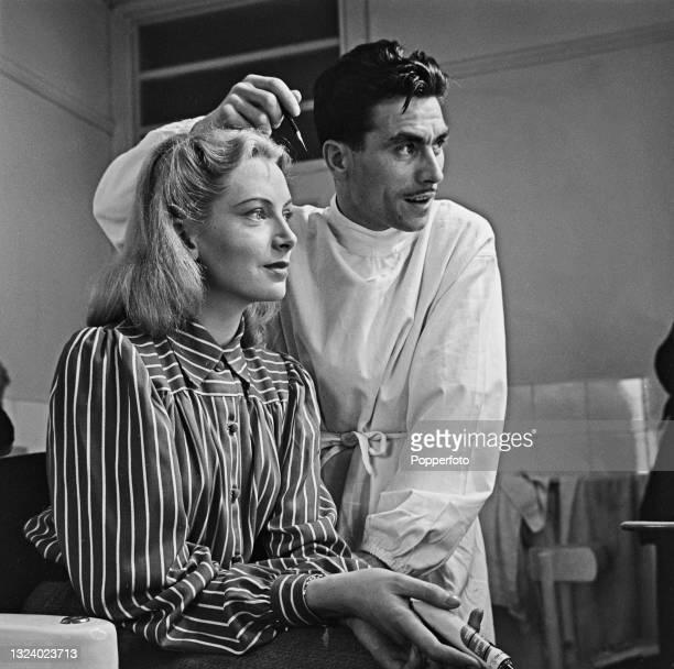 Scottish actress Deborah Kerr seated with Tony, her make-up artist, during shooting of the British film noir 'Hatter's Castle' at Denham Studios in...