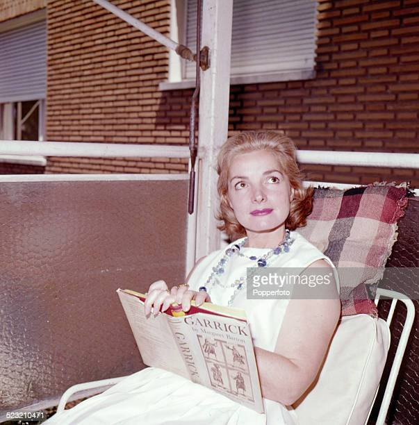 Scottish actress Elizabeth Sellars pictured wearing a white dress and seated on a lounger chair holding a biography of David Garrick in 1963