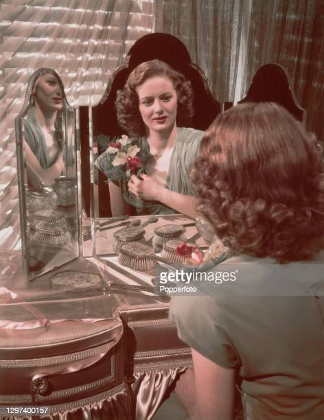 Scottish actress Elspet Gray pins an orchid flower spray to the shoulder of her evening dress whilst seated at her dressing table in front of a make...