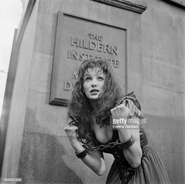 Scottish actress Lorna Heilbron wearing manacles outside the Hildern Institute For Mental Disorders, a fictional institution from the horror film...