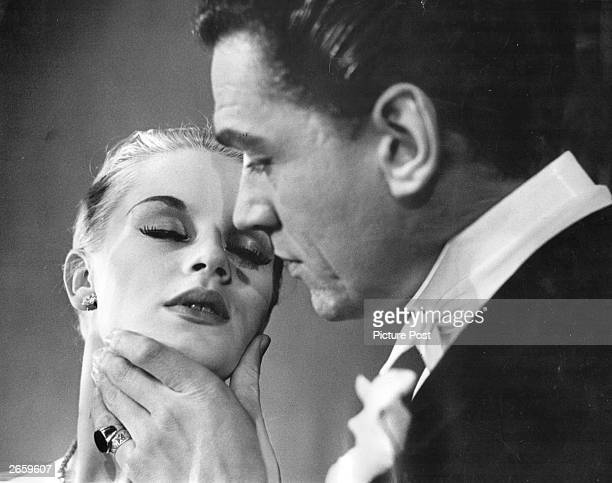 Scottish actress Mary Ure waits for a kiss from English actor Paul Scofield in a scene from the play 'Time Remembered'. Original Publication: Picture...