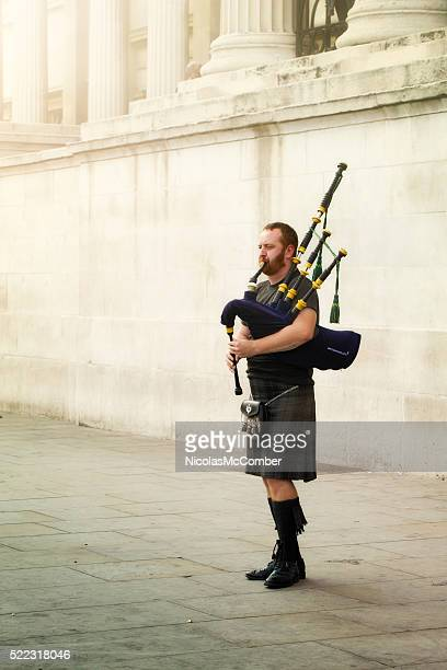 Scottish bagpipe player street of London foggy day