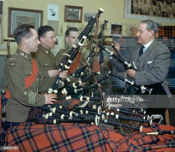 Scottish bagpipe player Willie Ross principal instructor at the Army School of Bagpipe Music and Highland Drumming pictured on right with some of his...