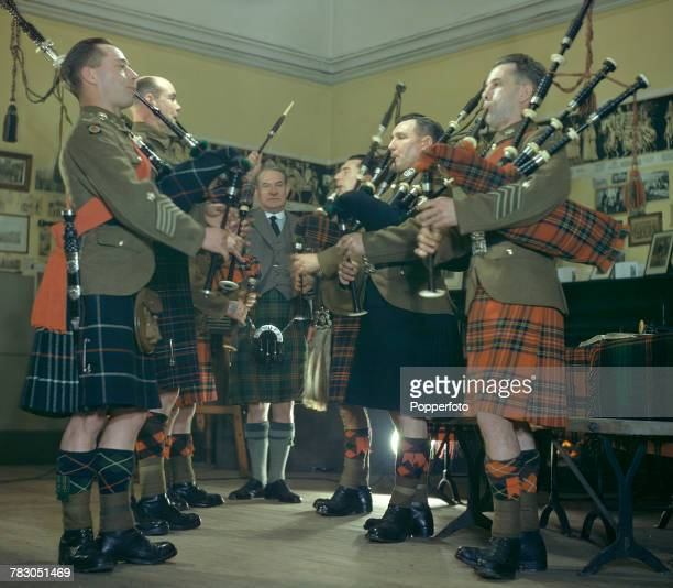 Scottish bagpipe player Willie Ross principal instructor at the Army School of Bagpipe Music and Highland Drumming pictured with some of his students...