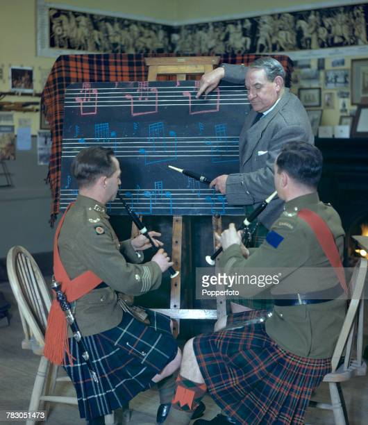 Scottish bagpipe player Willie Ross principal instructor at the Army School of Bagpipe Music and Highland Drumming pictured with two of his students...