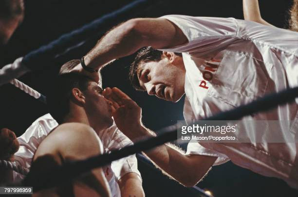 Scottish boxer Pat Clinton receives attention from his corner team trainer Jimmy Tibbs at the end of a round in his fight against fellow Scottish...