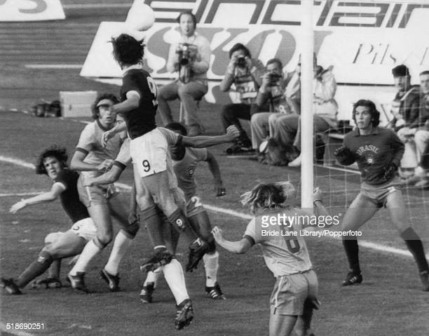 Scottish centreforward Joe Jordan heads the ball in an unsuccessful shot on the Brazilian goal during a World Cup group 2 match at the Waldstadion...