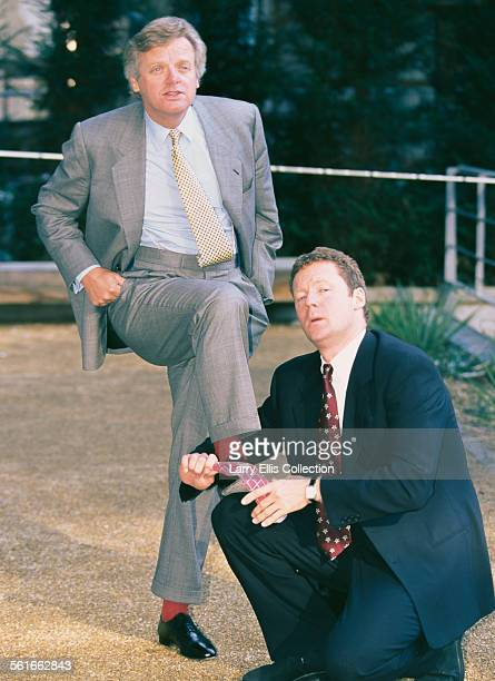Scottish comedian and impressionist Rory Bremner polishes the shoes of British businessman Michael Grade CEO of Channel 4 UK circa 1993