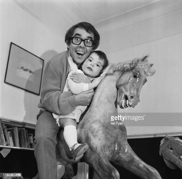 Scottish comedian Ronnie Corbett on a rocking horse with his daughter, Sophie, January 1969.