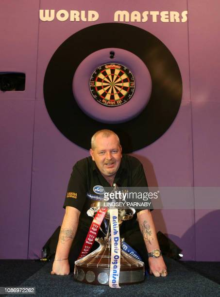 Scottish darts player Robert Thornton poses with the trophy after beating Briton Darryl Fitton on the final day in the Men's Final of the 2007 Winmau...