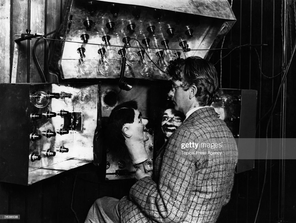 Scottish electrical engineer and television pioneer John Logie Baird (1888 - 1946) demonstrating his new invention the television with the aid of two ventriloquist's dummies. Baird was born in Helensburgh and studied at Glasgow University. Baird worked as an engineer at Clyde Valley Electric Power Company but had to retire due to ill health. He used his time to conduct experimental research into the transmission of images and gave a successful public display of his television system in London on 27th January 1926. In 1929 his mechanically scanned system was adopted by the BBC and he provided an improved system five years later. Baird also helped pioneer colour television and stereophonic sound.