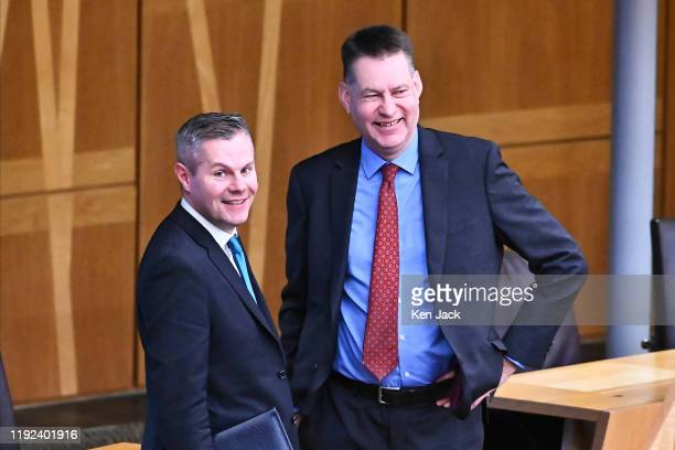 Scottish Finance Secretary Derek Mackay and Scottish Conservative Finance spokesperson Murdo Fraser stand together at the back of the chamber ahead...