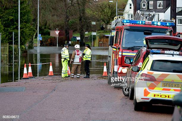 Scottish fire brigade personnel and police attending a flood
