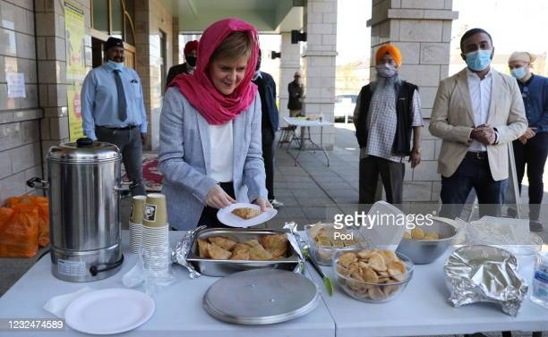 Scottish First Minister and leader of the Scottish National Party Nicola Sturgeon holds a plate with food as she visits the Gurdwara Guru Granth...