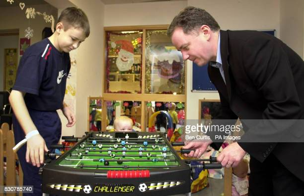 Scottish First Minister Jack McConnell plays table football with Brian Harvey who has appendicitis as twoyearold Zoe Thomson looks on in a games room...