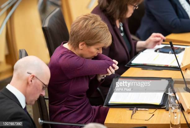 Scottish First Minister Nicola Sturgeon coughs into the crook of her arm as she holds First Minister's Questions in the debating chamber of the...