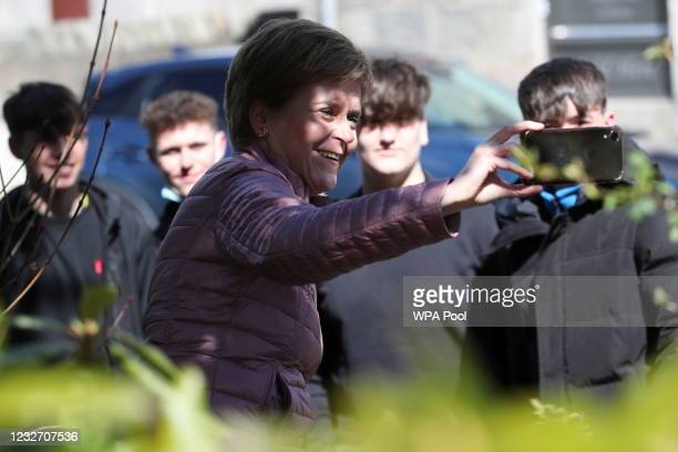 Scottish First Minister Nicola Sturgeon uses a smartphone to take a selfie as she campaigns for the parliamentary elections on May 5, 2021 in Alford,...