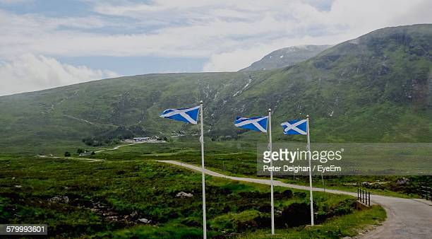 scottish flags by road against mountain - scotland flag stock photos and pictures