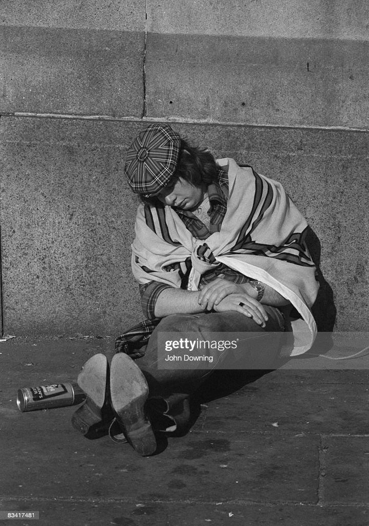 A Scottish football fan takes a nap in a London street, circa 1980.