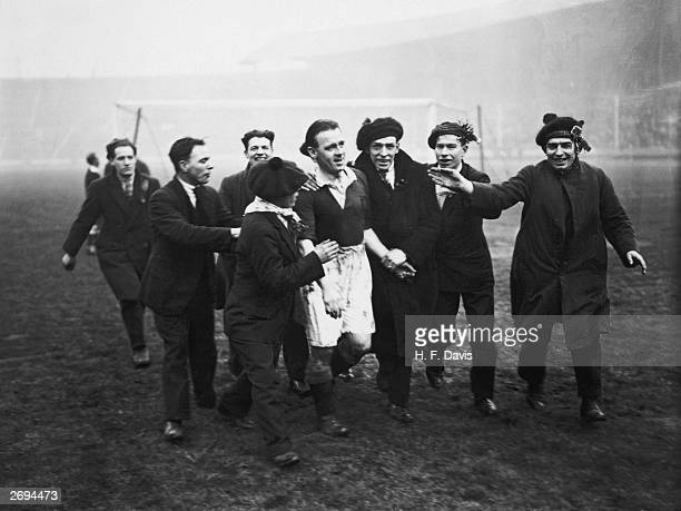 Scottish football fans escorting the Scottish captain James McMullan from the pitch at Wembley after Scotland had beaten England 51