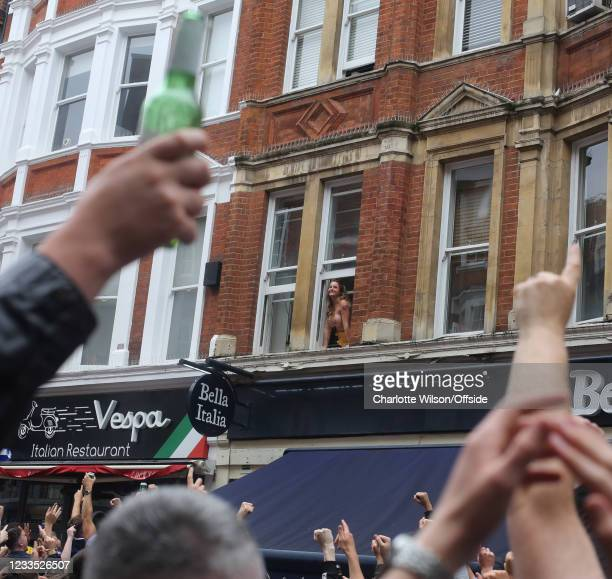 Scottish football fans in central London on the day of the UEFA Euro Football match against England, a woman bares her breasts from a first floor...