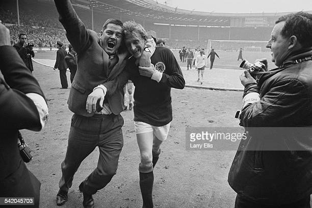 Scottish football player Denis Law is hugged by a fan after Scotland beat England 32 at an international match at Wembley Stadium London 15th April...