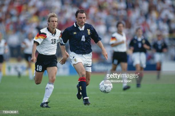 Scottish footballer Maurice Malpas makes a run with the ball as German footballer Jurgen Klinsmann chases during action in the group 2 match between...