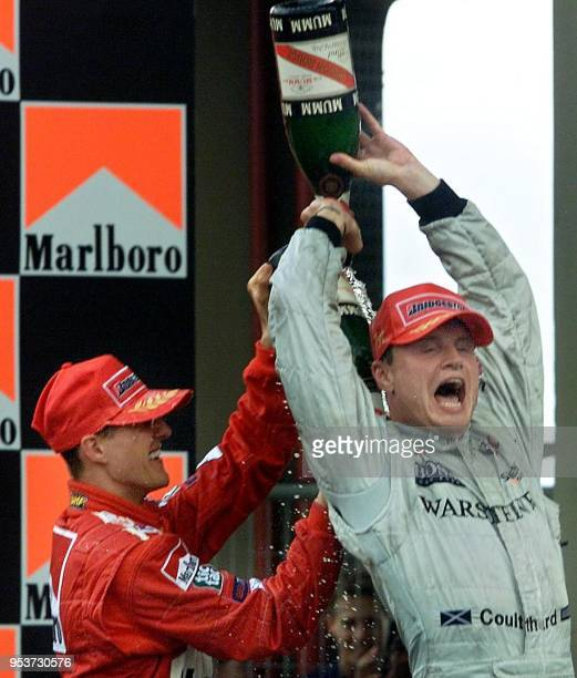 Scottish Formula One driver David Coulthard and German Michael Schumacher spray champagne celebrating Coulthrad's victory 01 April 2001 in the...