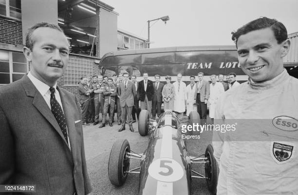 Scottish Formula One racing driver Jim Clark pictured on right with Colin Chapman founder of Lotus Cars and members of the Team Lotus motorsport crew...