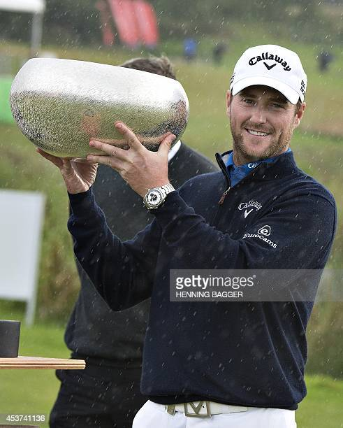 Scottish golfer Marc Warren holds his trophy after winning the finals of the European Golf Tour Made in Denmark 2014 at Himmerlands Golf and Spa in...