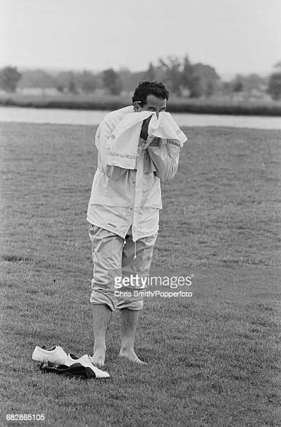 Scottish golfer Sam Torrance pictured bare foot and drying his face with a towel after playing a shot from water during action for Team Europe to win...