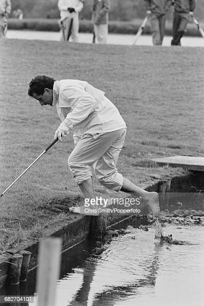 Scottish golfer Sam Torrance pictured bare footed as he exits a stream of water after playing a shot during action for Team Europe to win the 1985...